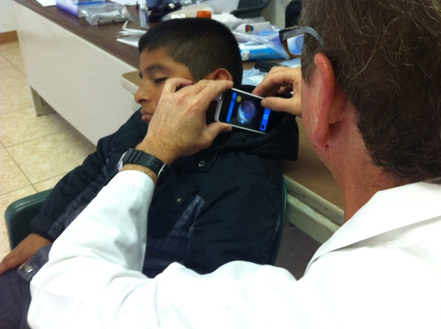 Dr. Kahn examining an ear of a patient in Mexico.